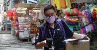 Курьер с защитной маской приносит доставку после новой вспышки коронавирусной болезни (COVID-19) в Гонконг. Архивное фото
