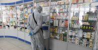 Человек в защитном костюме в одной из аптек. Архивное фото