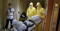 Медработники перевозят тело умершего от коронавируса COVID-19