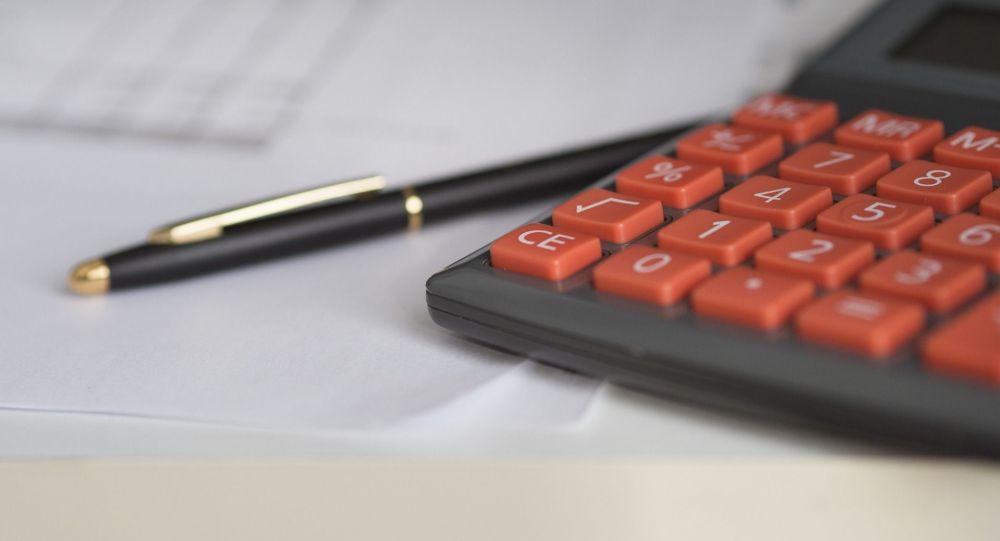 Калькулятор и бумаги с отчетами на столе. Иллюстративное фото