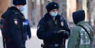 Москвада полициянын кызматкери өспүрүмдүн документтерин текшерип жатышат. Архив