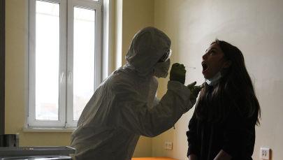 Медицинский работник берет у пациентки анализ на коронавирус. Архивное фото
