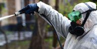 Сотрудник коммунальной службы проводит дезинфекцию внутридворовой территории. Архивное фото