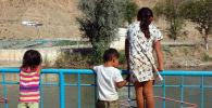 Дети смотрят на канал с моста в Оше. Архивное фото