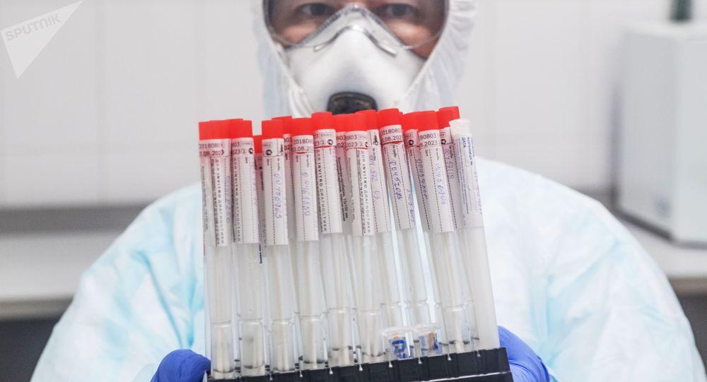 Сотрудник лаборатории держит в руках пробирки с биоматериалом для тестирования на коронавирусную инфекцию.