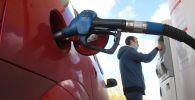 Мужчина оплачивает автомобильное топливо на одной из автозаправочных станций. Архивное фото