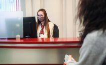 Сотрудница банка в защитной маске ведет прием посетителей. Архивное фото