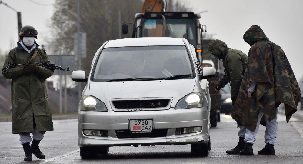 Военнослужащие Национальной гвардии, носящие лицевые маски, проверяют документы на контрольно-пропускном пункте, установленном за пределами Бишкека. Архивное фото