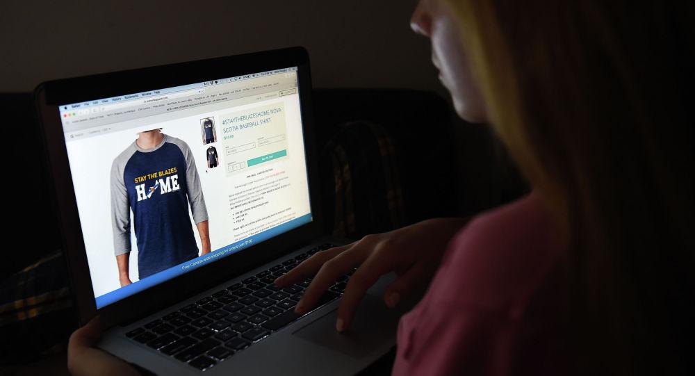 Девушка просматривает магазин одежды на ноутбуке. Архивное фото