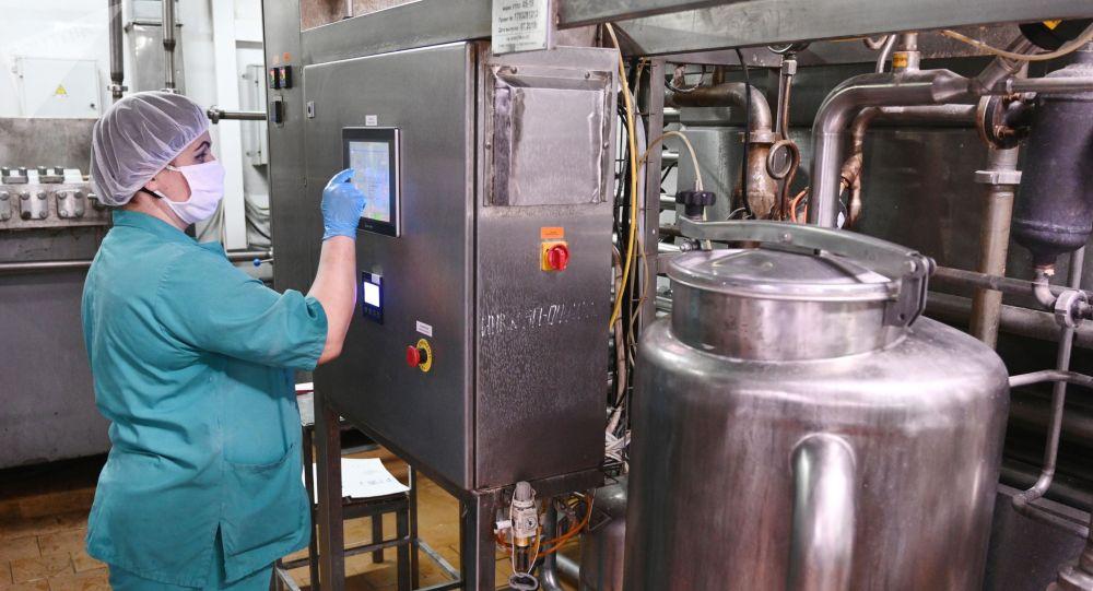 Сотрудница на линии производства молочной продукции предприятия. Архивное фото