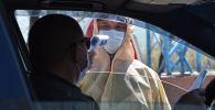 Медик проверяет температуру тела водителя на контрольно-пропускном пункте. Архивное фото