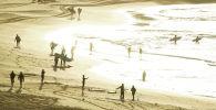 Люди занимаются серфингом, так как Bondi Beach вновь открывается для серферов и пловцов после его закрытия в Сиднее. Австралия, 28 апреля 2020 года