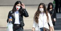 Девушки в медицинских масках на улице города. Архивное фото