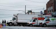 Сотрудники полиции Нью-Йорка охраняют грузовики с телами людей найденные в Бруклинском районе Нью-Йорка