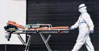 Медик карантинного центра везет носилки для пациента. Архивное фото
