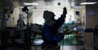 Медицинский работник, носящий средства индивидуальной защиты (СИЗ), работает в отделении интенсивной терапии. Архивное фото