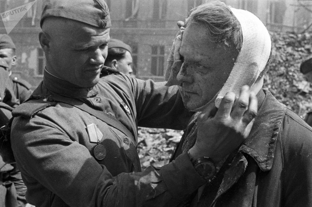 Советская армия помогала и раненым берлинцам. Медицинскую помощь им оказывали прямо на улице.