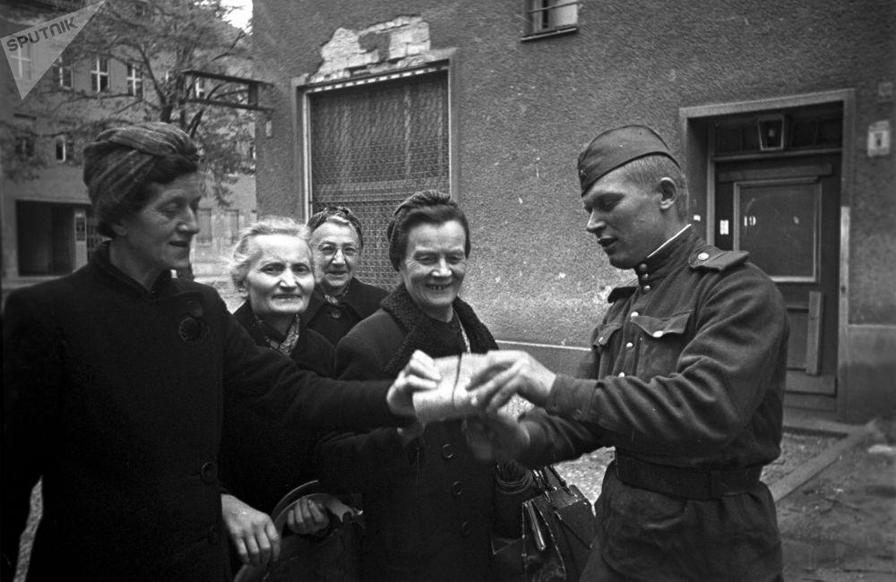 Советский солдат раздает хлеб женщинам в Берлине