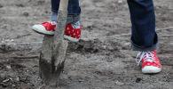 Подросток копает землю. Архивное фото