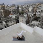 Мужчина и женщина занимаются йогой на крыше многоэтажного дома в Бейруте (Ливан)