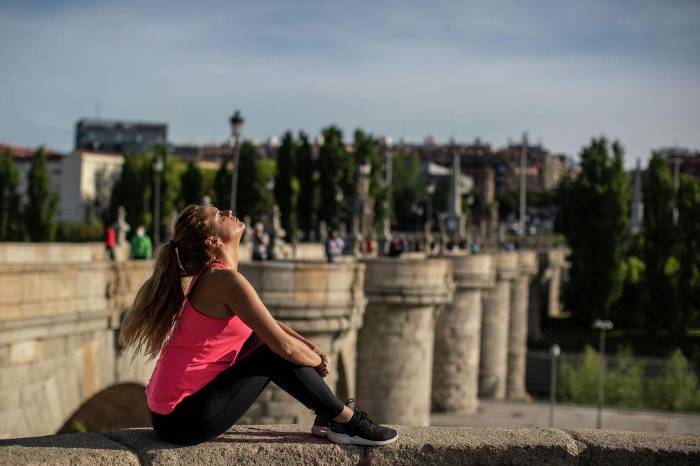 Девушка загорает сидя на мосту Толедо в Мадриде (Испания)