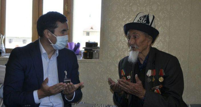 Полномочный представитель правительства по Ошской области Узарбек Жылкыбаев во время вручения ветеранам ВОВ в Кара-Суйском районе по 10 тысяч сомов