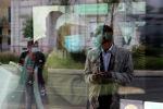 Человек в защитной маске, ожидающий на остановке, отражается в окне автобуса