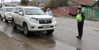 Сотрудник патрульной милиции регулирует движение на блокпосту в Бишкеке