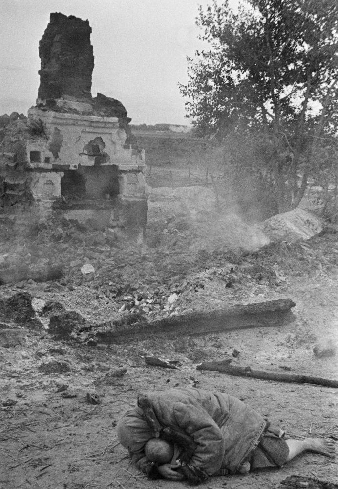 Мать закрывает собой ребенка во время обстрела. Деревня Красная Слобода, Брянский фронт, 1941 год.