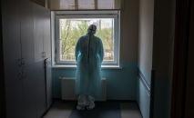 Врач стоит у окна больницы. Архивное фото