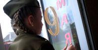 Юная участница всероссийской акции Окна Победы украшает к празднику 9 мая окно своей квартиры. Архивное фото