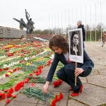 Латвияда Өлбөс полк акциясынын уюштуруучусу Маргарита Драгиле Бошотуучулар эстелигине блокадачы чоң энесинин сүрөтү менен келди