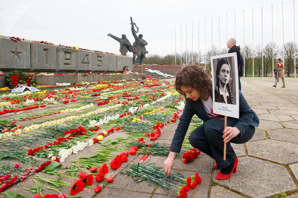 Организатор Бессмертного полка в Латвии Маргарита Драгиле пришла к памятнику Освободителям с портретом бабушки-блокадницы