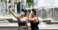 Девушки фотографируются на площади Кастелло в Милане.