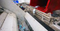 Бир жолу колдонулган маскаларды таштанды контейнерден ташуучу унаага түшүрүү. Архив
