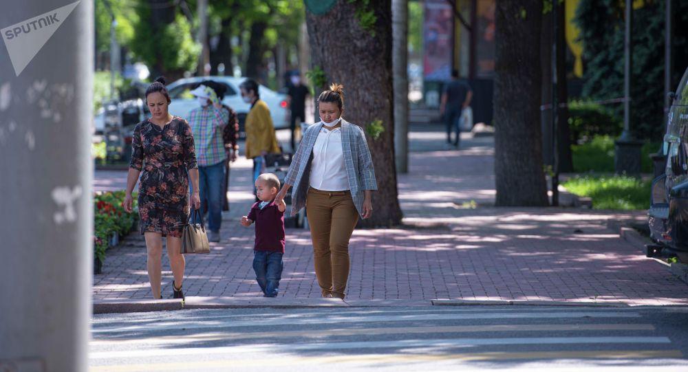 Горожане идут по одной из улиц, после завершения режима чрезвычайного положения в Бишкеке