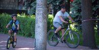 Бишкекте өзгөчө кырдаал аяктагандан кийин эркек киши менен бала велосипед тээп жатышат