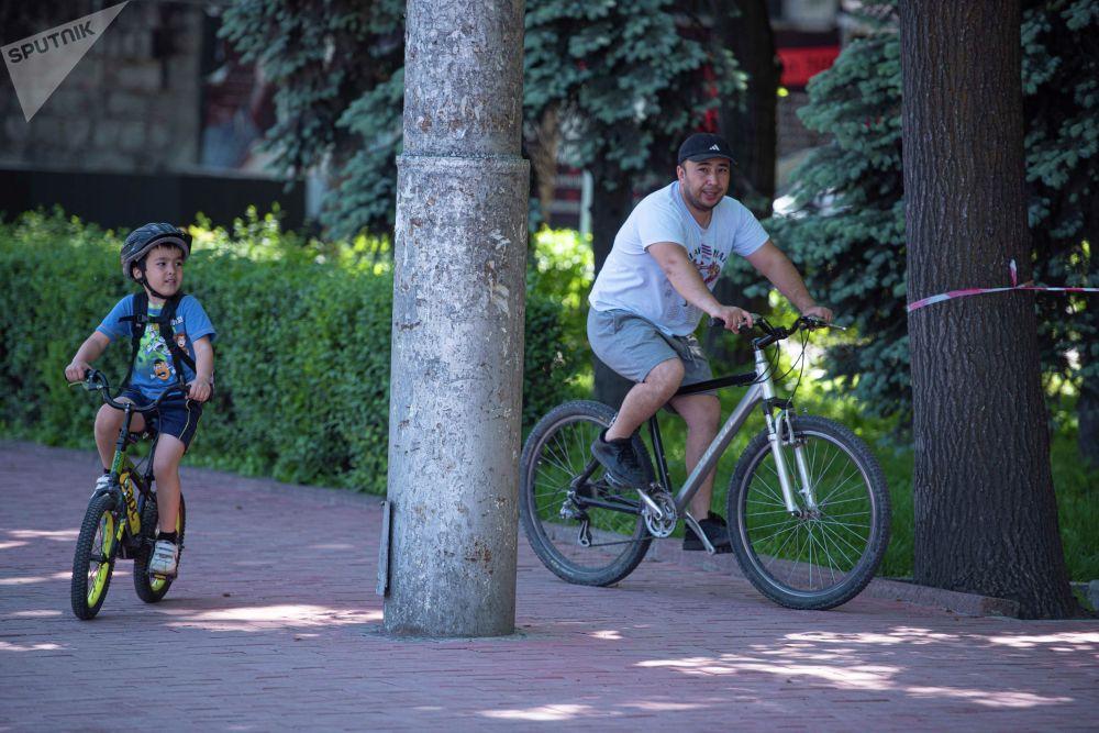 Мужчина и ребенок катаются на велосипеде, после завершения режима чрезвычайного положения в Бишкеке
