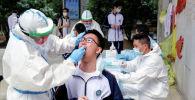 Медики в защитных костюмах забирают мазки у старшеклассников для тестирования на коронавирус.