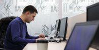 Мужчина за работой на компьютере в кабинете бизнес-инкубатора. Архивное фото
