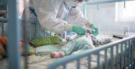 Врач в защитном костюме осматривает младенца. Архивное фото