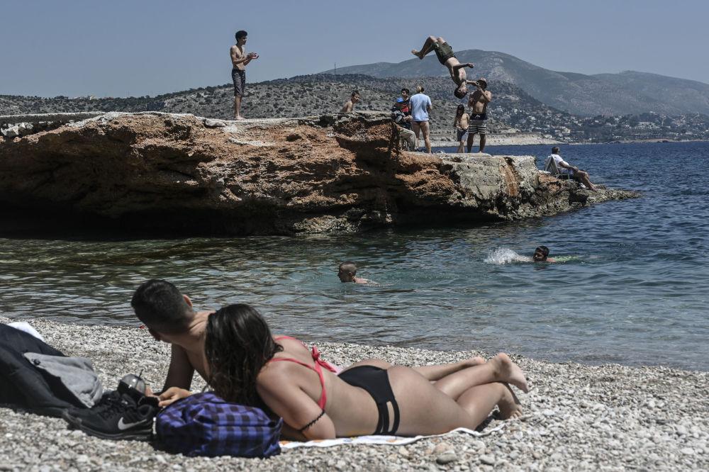 Отдыхающие на пляже в пригороде Афин