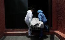 Работники похоронного бюро несут тело человека скончавшегося от COVID-19. Архивное фото