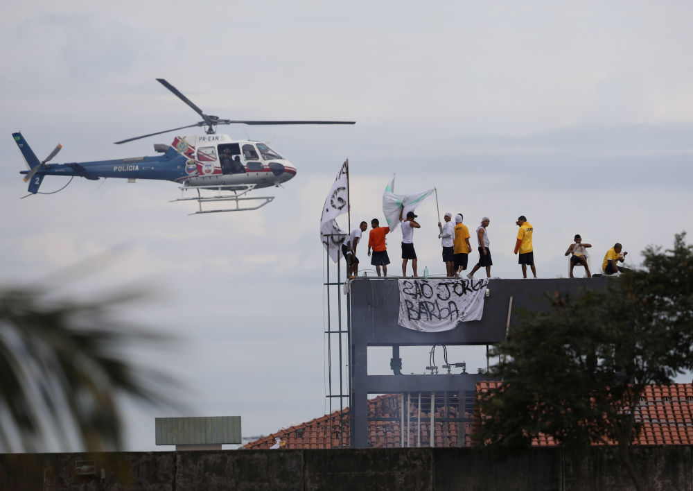 В тюрьме Пуракеквара в Мануасе (Бразилия) начался бунт из-за вспышки COVID-19.  На фото: полицейский вертолет пролетает над крышей тюрьмы, где произошли беспорядки.