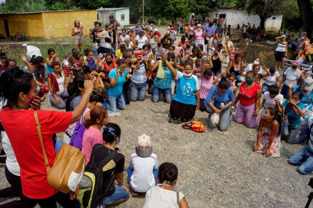 В результате беспорядков в тюрьме Лос-Льянос в Гуанаре (Венесуэла) погибли десятки людей.  На фото: родственники заключенных молятся, узнав о бунте.