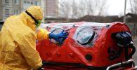 Врач бригады скорой помощи в защитном костюме готовит бокс для перевозки. Архивное фото