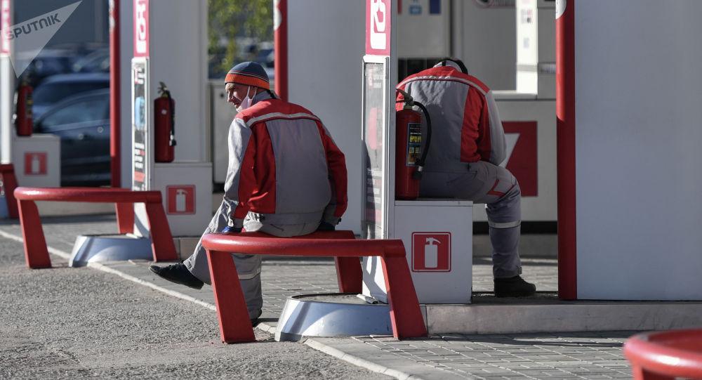 Сотрудники на автомобильной заправочной станции в ожидании клиентов. Архивное фото