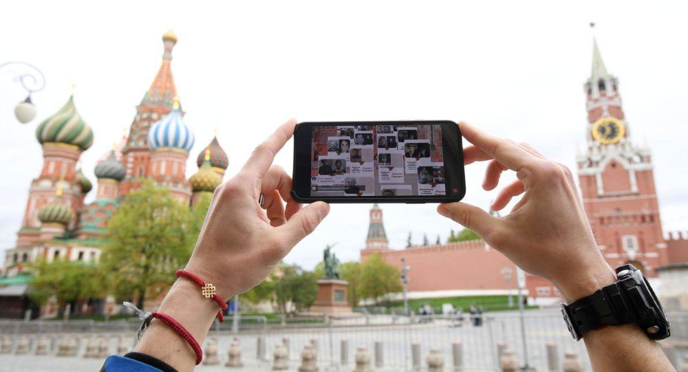 Киши Москвадагы Кызыл аянтта Өлбөс полктун трансляциясын көрүп жатат. Архив