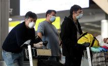 Пассажиры в аэропорту в медицинских масках. Архивное фото
