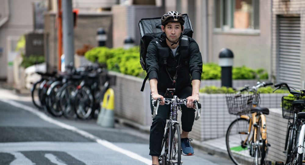 Серебряный призер Олимпийских игр 2012 года японский фехтовальщик Ре Мияки во время работы курьером в Токио